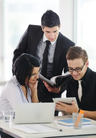 Three business people working at office with paperwork using tablet and laptop Stock Photo - 19265804