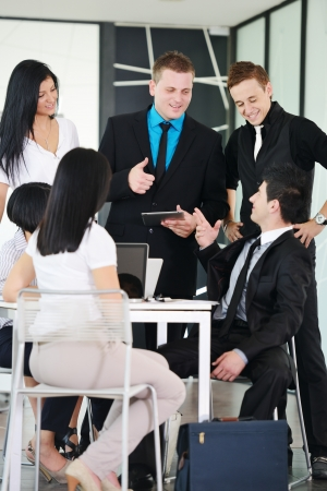 Business executives at a meeting discussing a work photo