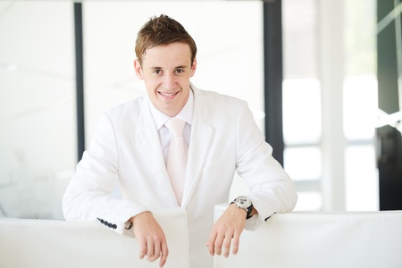 Young businessman standing in modern office lobby with copy space photo