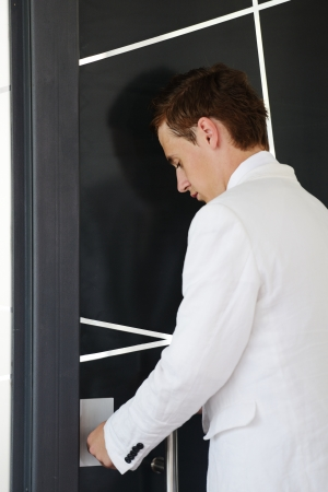 out of doors: Young businessman standing in modern office lobby and opening door