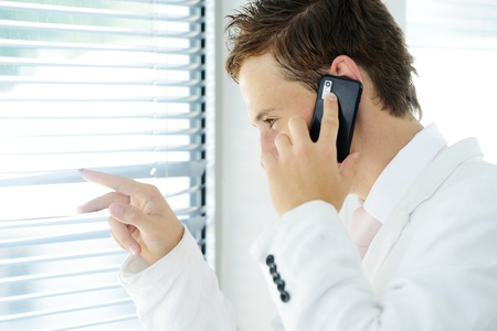 Young businessman looking through blinds whilst making call photo