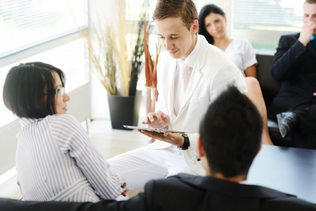 Portrait of modern couple talking to manager while discussing conditions of mortgage using tablet Stock Photo - 19265577