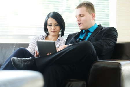 Young businessman and business woman sitting at office lobby on leather sofa working with tablet pc photo