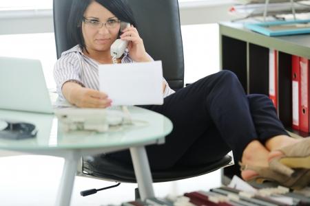 female boss: Junge Unternehmerin sitzt in einem B�rostuhl und Arbeitsbedingungen, Chefin