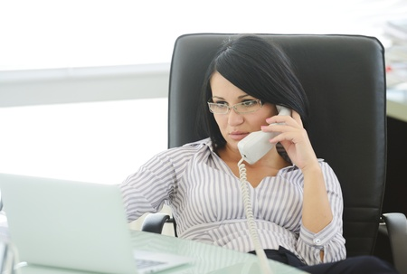 Young businesswoman sitting in an office chair and working, female boss photo