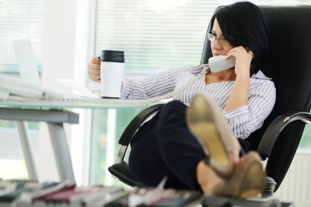 executive chair: Young businesswoman sitting in an office chair and working, female boss
