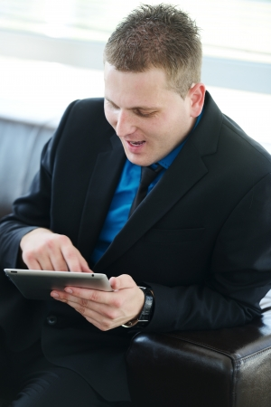 Businessman sitting on leather sofa using tablet photo