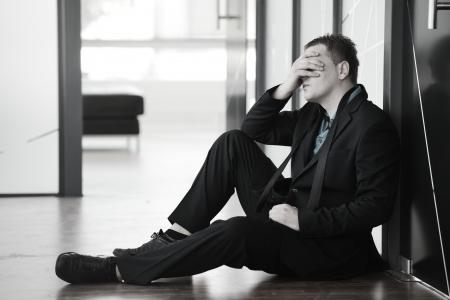 Portrét zdůraznil zklamaný podnikatel sedí sám na podlaze v kanceláři