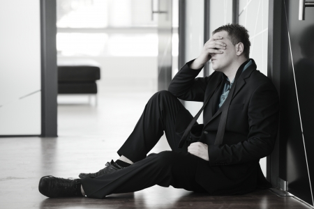 recession: Portrait of a stressed disappointed businessman sitting alone on floor in office