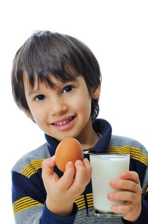 Cute little kid with glass of milk and egg photo