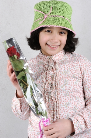 Cute little girl holding red rose Stock Photo - 19264886