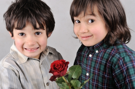 Two boys with beautiful red rose photo