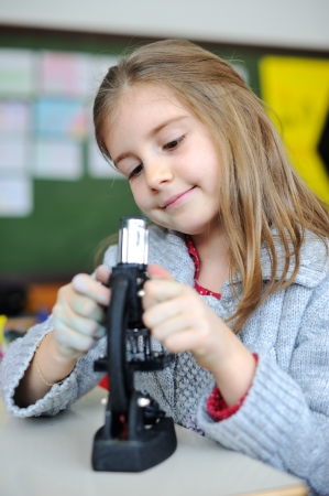 science class: Beautiful young girl with a miscroscope