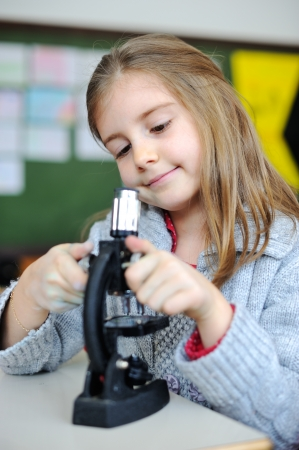 Beautiful young girl with a microscope photo