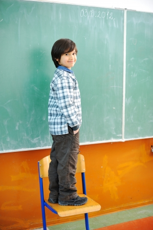 schooltime: Cute boy standing on a chair in front of blackboard