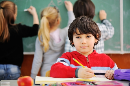 Roztomilý malý školák kreslení jablko a díval se na kameru