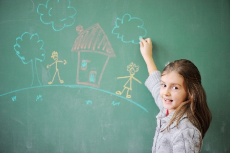 mulatto: Cute little girl drawing on blackboard