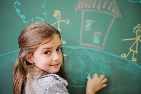 children health: Cute little girl drawing on blackboard
