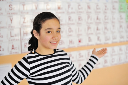 Beautiful girl standing in front of a periodic table of elements photo