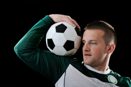 proffessional: Proffessional footballer holding a ball on his shoulder