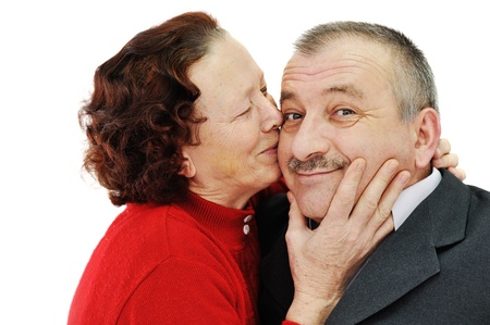 Senior woman kissing in a cheek her husband isolated over white background photo
