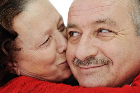 Closeup image of elderly woman kissing in a cheek her husband photo