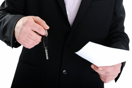 sell car: Businessman handing a key with paper agreement Stock Photo