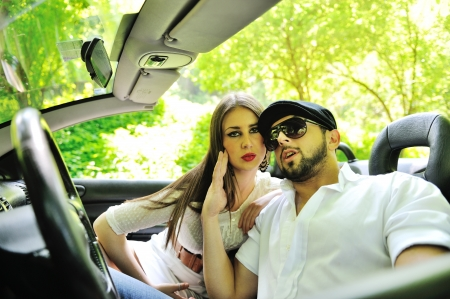 Young couple hanging together in car outdoors photo