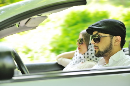 Young couple enjoying in car at fast pace photo
