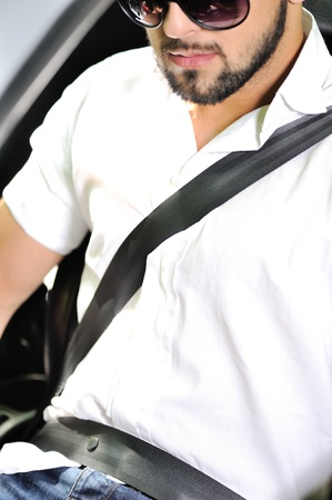 car safety: Young man in sunglasses sitting in a car with seatbelt on