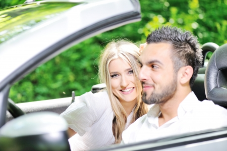 Young lovers in a sports car photo