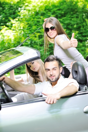 Three friends in a sports car with thumbs up