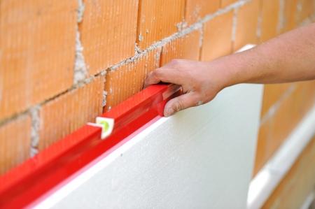 styrofoam: Worker checking horizontal level with leveling tool