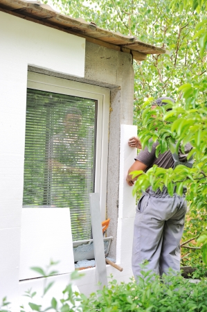 Construction worker applying foam to exterior house wall photo