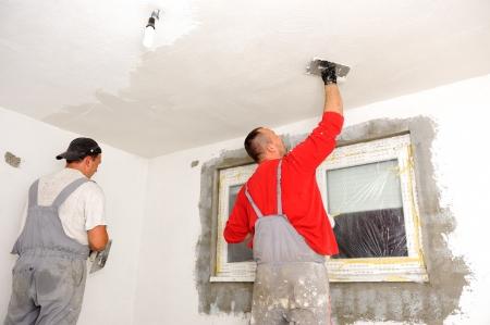 renovation de maison: Travailleurs de la construction peindre les murs
