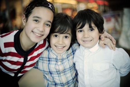 Three kids outside of shopping mall at night photo