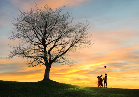 three children: Children playing on beautiful meadow with tree Stock Photo