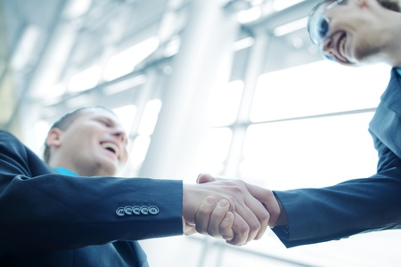 business  deal: Business shaking hands in front of modern building with copy space (selective focus)