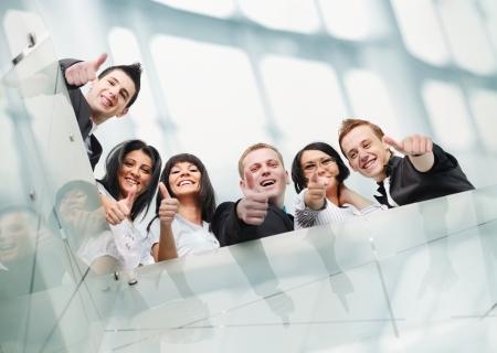 Skupina podnikatelů v kanceláři s palci nahoru