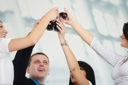 Business group celebrating a victory holding glasses with drink photo