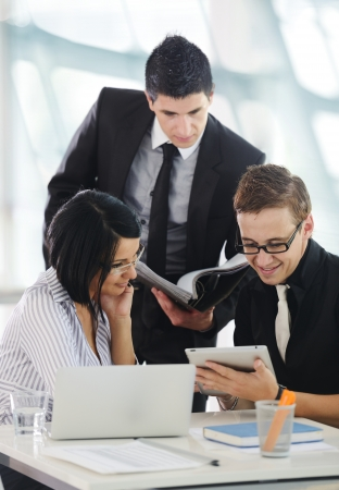 woman searching: Three business people working at office with paperwork using tablet and laptop Stock Photo