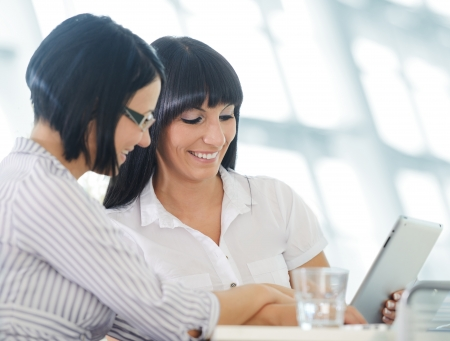 women talking: Two cheerful smiling young business women working at office Stock Photo