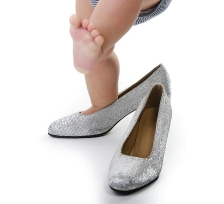 pied jeune fille: Petit enfant jouant whit chaussures argent�es maman