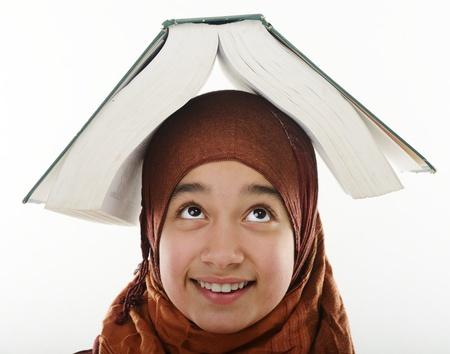 petite fille musulmane: Femme arabe étudiant équilibrage grand livre sur la tête