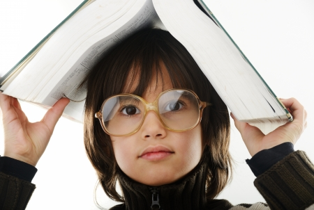 Student child with a book and glasses over his head isolated over white background photo