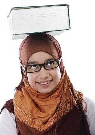 arab teen: Female Arabic student balancing big book on head