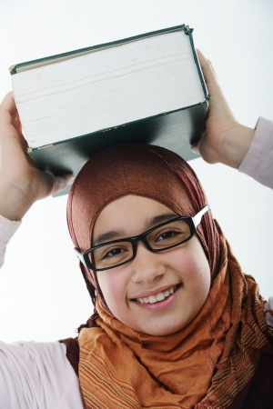 Female Arabic student balancing big book on head photo