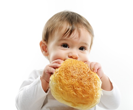 baby girls smiley face: Baby eating bun bread Stock Photo