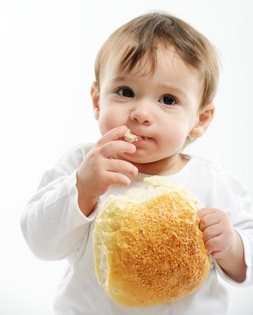 baby girls smiley face: Baby eating bun bread Stock Photo