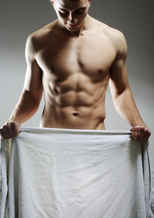 A nude young man covering himself with a towel  as copy space